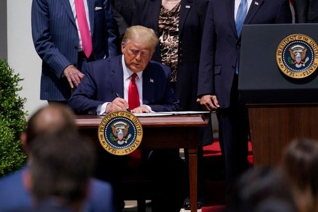 ئامېرىكا پرېزىدېنت دونالد ترامپ قانۇن لايىھەسىگە ئىمزا قويۇۋاتقان كۆرۈنۈش. 2020-يىلى 5-ئىيۇن، ۋاشىنگتون