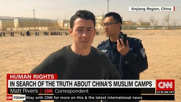 CNN مۇخبىرى ئۇيغۇر رايونىدىكى مەلۇم جازا لاگېرىغا يېقىنلاشقاندا، خىتاي ساقچىلىرى تەرىپىدىن توسۇۋېلىنغان كۆرۈنۈشى.