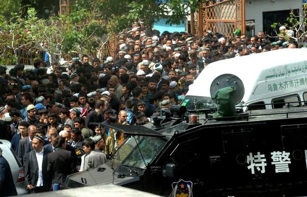 Xitay alahide qoralliq saqchilirining jüme namizidin qaytqan Uyghurlarni nazaret qiliwatqan körünüsh. 2014-Yili 23-may, ürümchi.