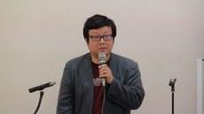 ئوبزورچى مىۇرا كوتارو ئەپەندىم يىغىندا سۆز قىلماقتا. 2016-يىلى 30-ئىيۇل، توكيو.
