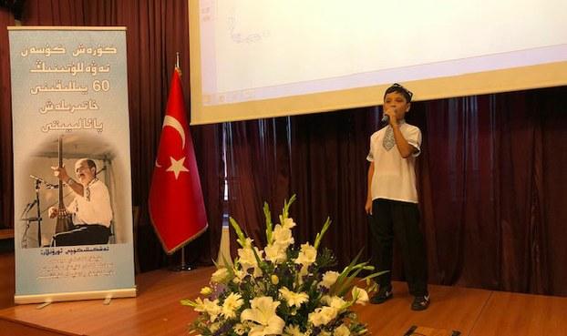 Tonulghan sen'etkar merhum küresh küsen tewellutining 60-yilliqi xatirilesh murasimida Uyghur ösmür déklamatsiye qilmaqta. 2019-Yili 6-séntebir, istanbul.