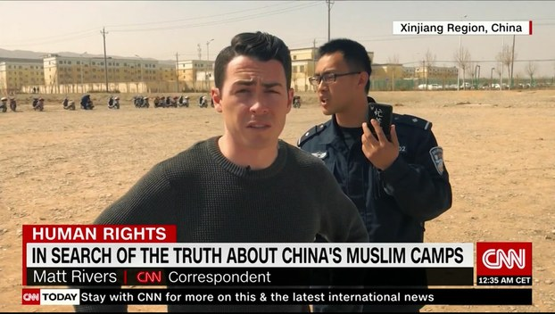 CNN مۇخبىرلىرى قەشقەر شەھىرىنىڭ سىرتىدىكى مەلۇم بىر جازا لاگېرىغا يېقىنلاشقاندا خىتاي ساقچىلىرىنىڭ ئۇلارنى توسۇۋالغان كۆرۈنۈشى.
