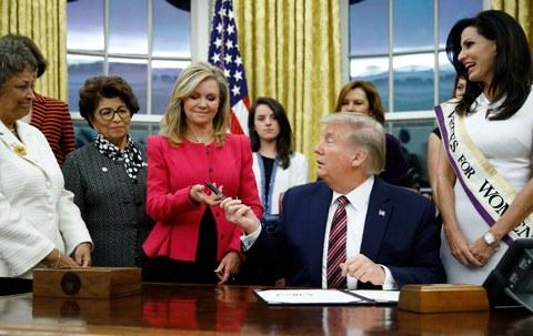 پرېزىدېنت دونالد ترامپ ئاقساراينىڭ ئوۋال ئىشخانىسىدا قانۇنىغا ئىمزا قويغاندىن كېيىن، ئامېرىكا كېڭەش پالاتا ئەزاسى مارشا بلەكبېرن خانىمغا قەلەم سۇنغان كۆرۈنۈش. 2019-يىلى 25-نويابىر، ۋاشىنگتون.