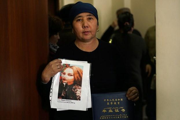 Nurbaqiyt kali'askar Uyghur rayonidiki jaza lagérigha solan'ghan qizi rezila nulalening süriti we mektep püttürüsh diplomini tutup turghan körünüsh. 2018-Yili 6-dékabir, qazaqistan.