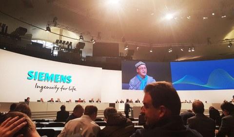 Gérmaniye zéminis (Siemens) shirkitining yilliq pay chéki hessidarlar yighinida, d u q ning wekili esqer jan(ékranda) kishilik hoquq teshkilatlirigha wakaliten söz qilmaqta. 2020-Yili 5-féwral, myunxén.