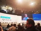 گېرمانىيە زېمىنىس (Siemens) شىركىتىنىڭ يىللىق پاي چېكى ھەسسىدارلار يىغىنىدا، د ئۇ ق نىڭ ۋەكىلى ئەسقەر جان(ئېكراندا) كىشىلىك ھوقۇق تەشكىلاتلىرىغا ۋاكالىتەن سۆز قىلماقتا. 2020-يىلى 5-فېۋرال، ميۇنخېن.
