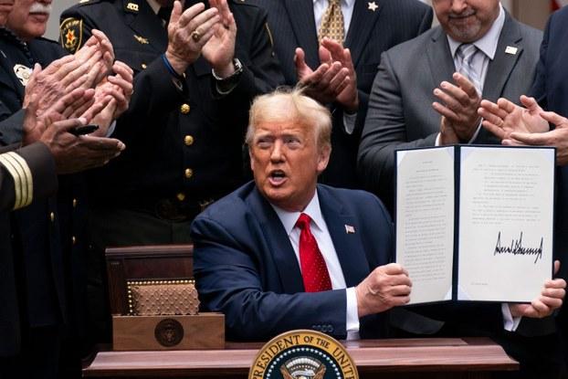 ئامېرىكا پرېزىدېنت دونالد ترامپ قانۇن لايىھەسىگە ئىمزا قويۇۋاتقان كۆرۈنۈش. 2020-يىلى 16-ئىيۇن، ۋاشىنگتون