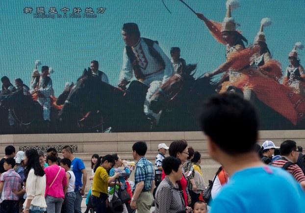 Tyen'enmén meydanida xitay sayahetchilerni qiziqturush üchün Uyghur rayonidiki az sanliq milletlerning bayrimi körsitiliwatqan téléwiziye ékrani etrapigha yighilghan xitay sayahetchiler. 2014-Yili 1-may, béyjing.